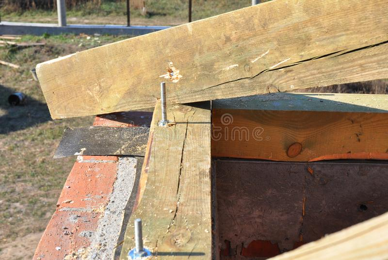 Roofing construction. Installing wooden rafters, frame timber with bitumen waterproofing on house roof corner. Close up stock images