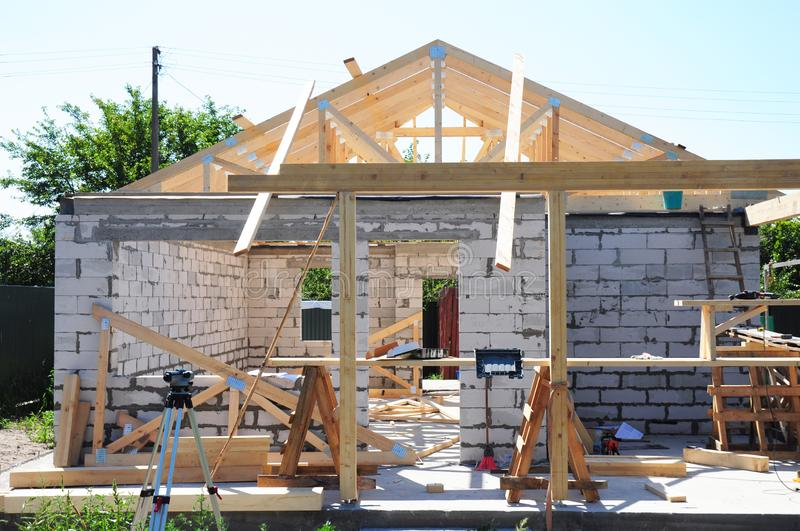 Roofing construction with wooden frame beams, timber, trusses and house construction aerated concrete blocks work. Close up stock photography
