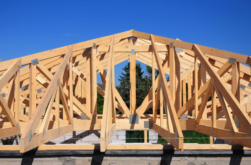 Roofing Construction. Wooden roof frame house construction with wooden roof beams, trusses, timber. Close up stock photo