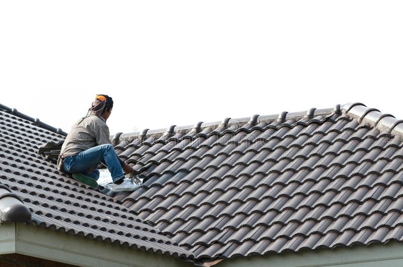 Roofing - construction worker standing on a roof covering it wit stock photo