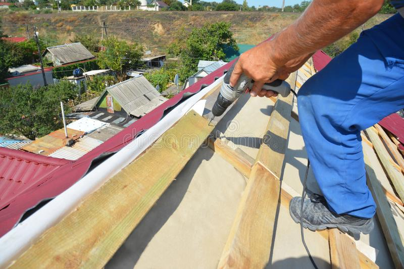 Roofing contractor installing metal roof tile for roof repair. Roofer install metall roof sheets with driver. Close up stock photos