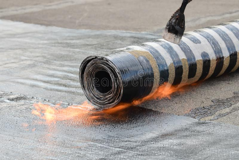 Roofing installation felt with heating and melting bitumen roll by torch on flame, closeup detail shoot stock photos