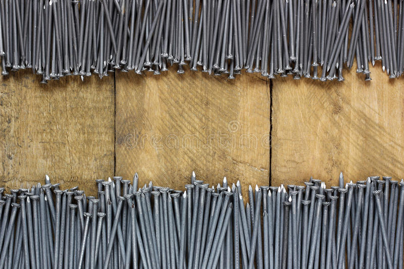 Roofing nails on a wooden platform, top view. Background of roofing nails on a wooden platform, top view. empty place for Your text in the center royalty free stock image