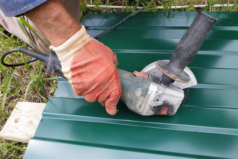 During the roofing work, a construction worker sprays a steel sheet with a trapezoidal profile with an angle grinder stock photos