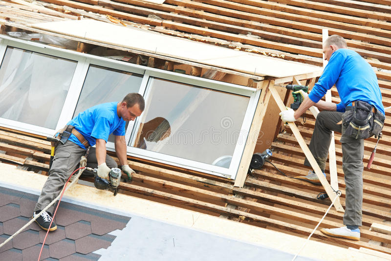 Roofing work with flex roof. Worker on roof at works with flex tile material mounting roofing royalty free stock images