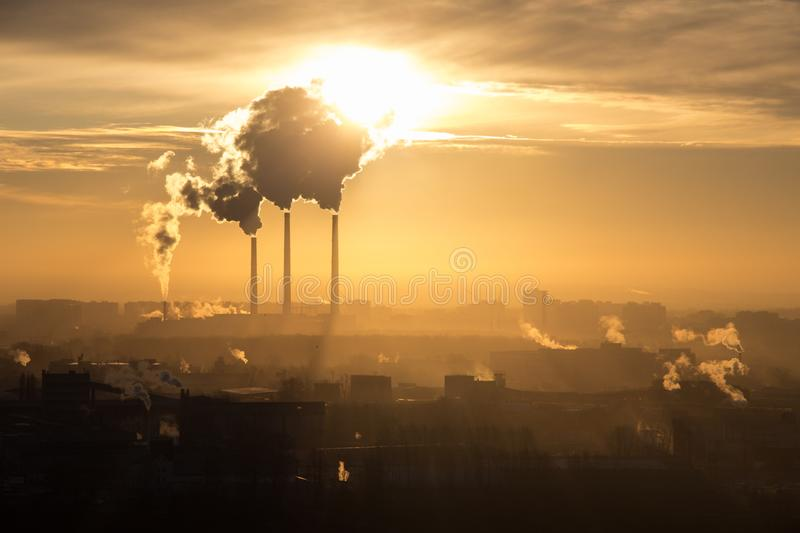 Roofs of city houses during sunrise.Dark smoke coming from the thermal power plant pipe. Factory smoke, polluting the atmosphere. stock images
