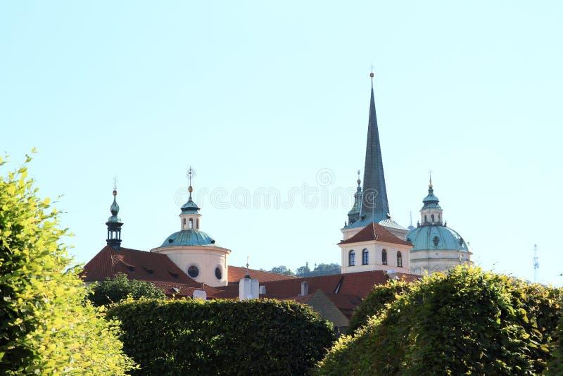 Roofs of Prague churches. Behind bush - green fence of Wallenstein garden in Prague (Czech Republic stock images