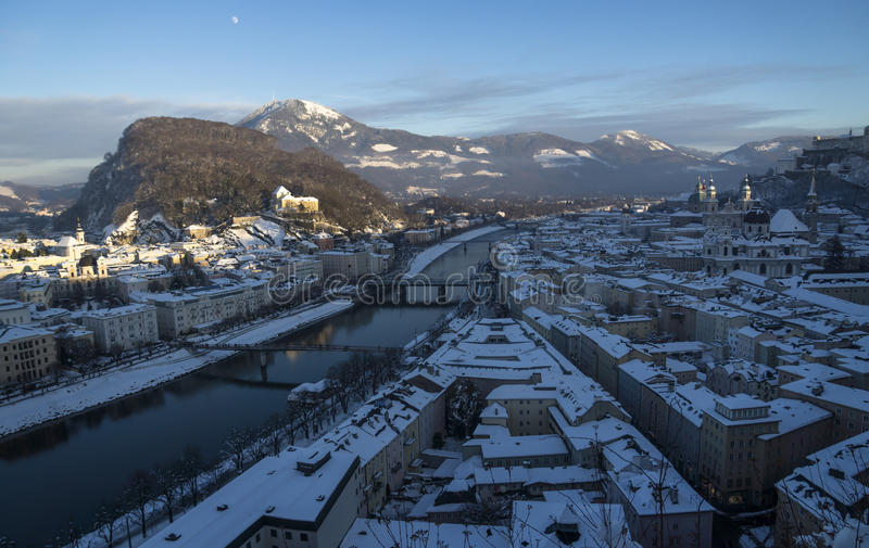 Roofs with snow, overview over Salzburg old town. Shortly before sun is setting stock images