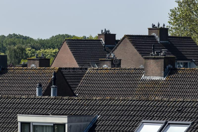 Roofscape tiled roofs Barendrecht Netherlands. A roofscape of tiled roofs in Barendrecht, the Netherlands. Showing brown rooftiles, dormers and chimneys royalty free stock photography