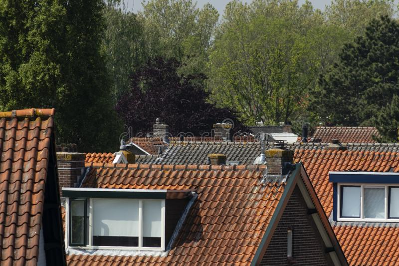 Roofscape tiled roofs Barendrecht Netherlands. A roofscape of tiled roofs in Barendrecht, the Netherlands. Showing orange rooftiles, dormers and chimneys royalty free stock image