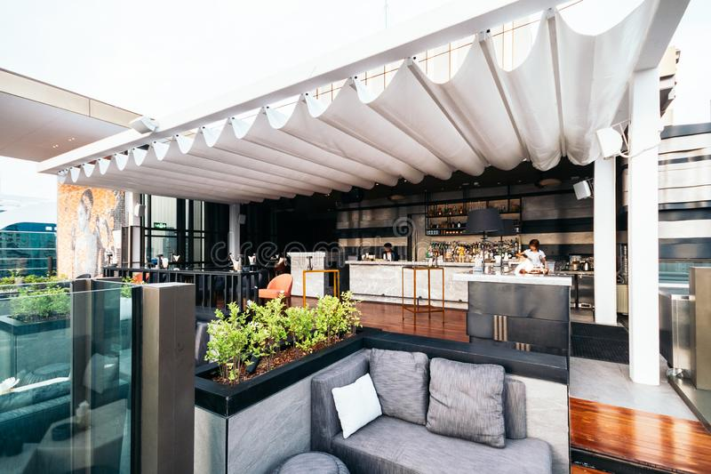 Rooftop bar with white movable roof and outdoor sofa royalty free stock photography