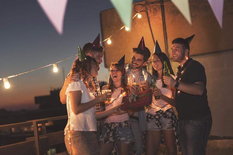Rooftop birthday party. Group of young friends having a birthday party at a building rooftop, singing a song and blowing a candle. Focus on the people in the royalty free stock images