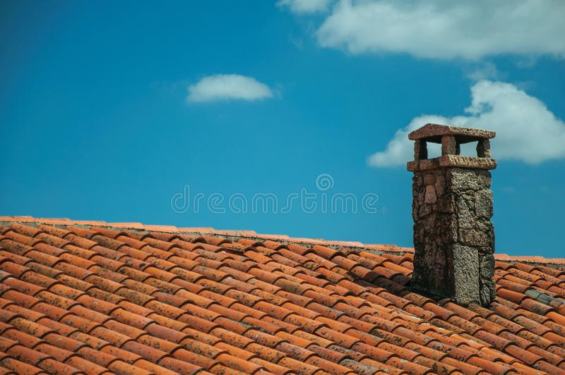 Rooftop covered by shingles and stone chimney stock image