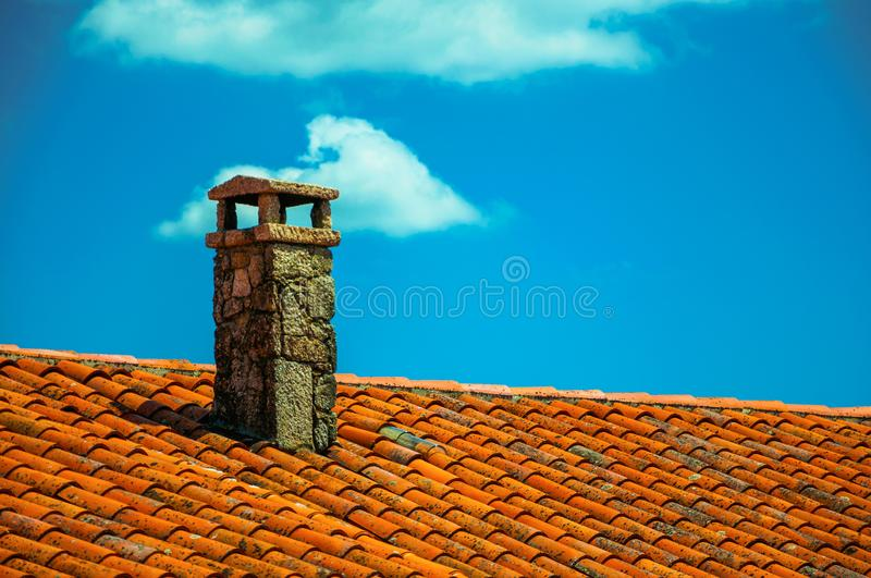 Rooftop covered by shingles and stone chimney royalty free stock photo