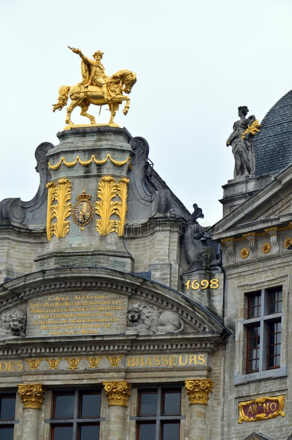 Rooftop sculptures of opulent buildings at Grand Place, Brussels City, Belgium. Brussels, Belgium - April 2015: Rooftop sculptures of opulent buildings at Grand royalty free stock image