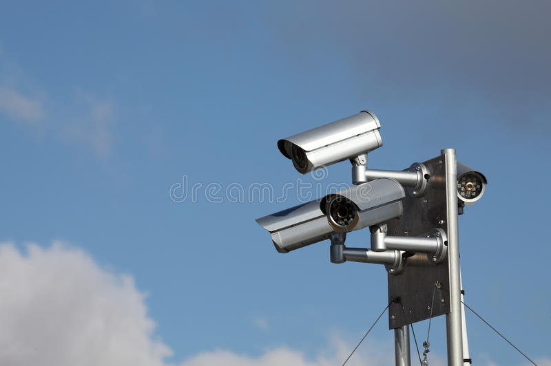 Rooftop Security Surveillance Cameras. A close up of a rooftop unit with four security cameras providing surveillance in many directions against a blue sky royalty free stock image