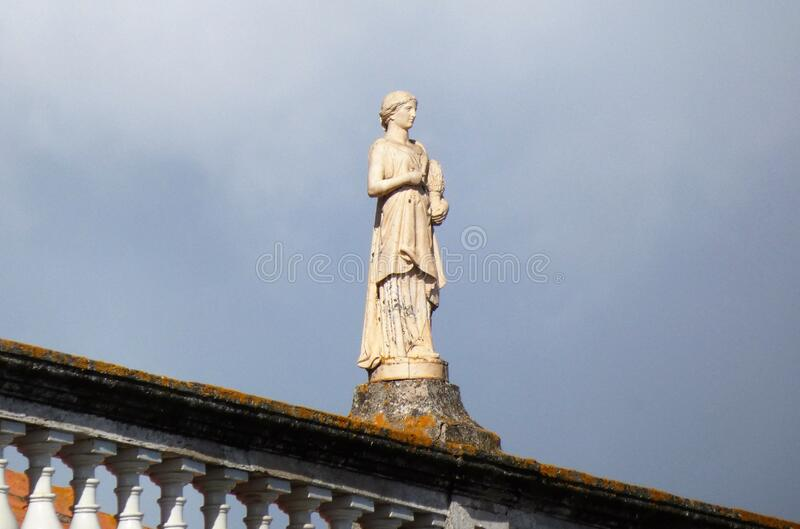 Rooftop Statue in Old Portimao. This lovely old statue graces a rooftop in old Portimao and is striking contrast to the sky royalty free stock photography