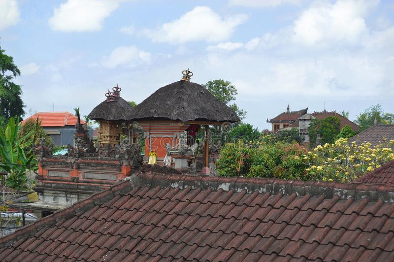 Rooftop View of Thatched Roof Shrines. In Ubud The people of Bali envelope themselves in their religion. Many families have shrines built on the rooftops of stock images