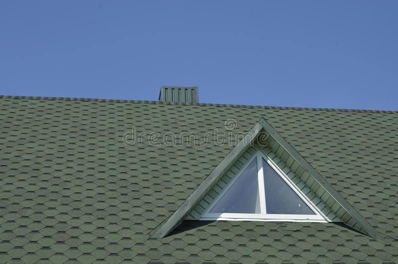 Rooftop with window against blue sky