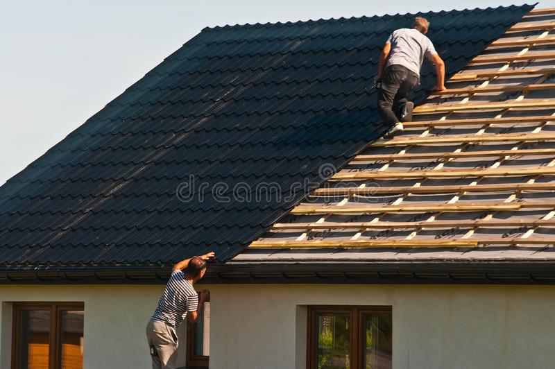 Rooftop worker installing new metal tiles on a house. Poland, August 2019: an anonymous roofer or rooftop worker installing new metal roof on a newly constructed stock photos