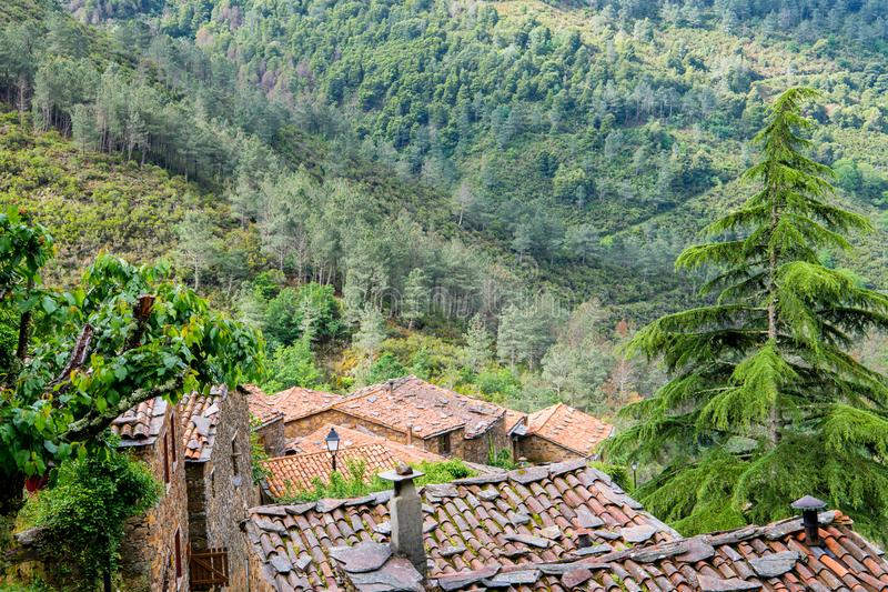 Tiled rooftops of an old European village below a forested mountainside in Portugal stock photos