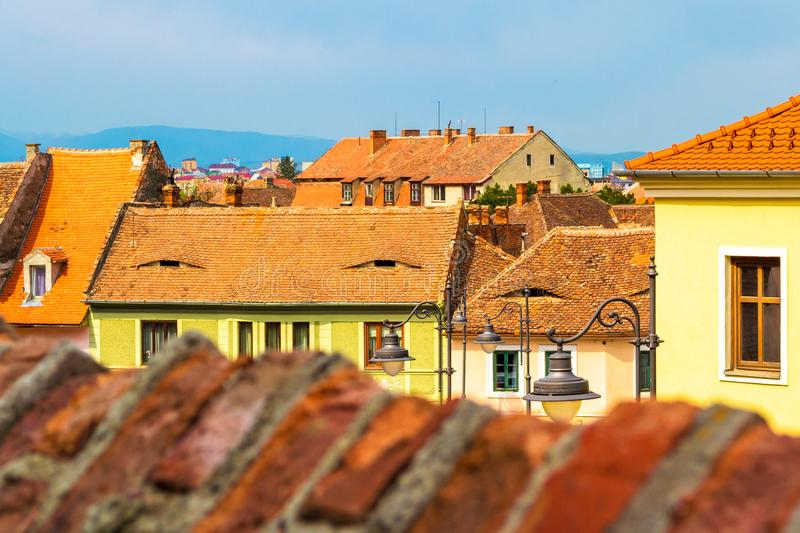 Rooftops with windows shaped like eyes and medieval style architecture in Sibiu Hermannstadt, Romania, on a hot, sunny day. royalty free stock image