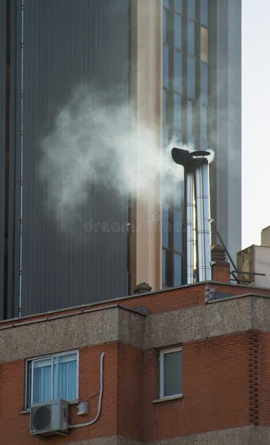 Rook die van een schoorsteen van een gebouw tussen wolkenkrabbers toenemen royalty-vrije stock foto's