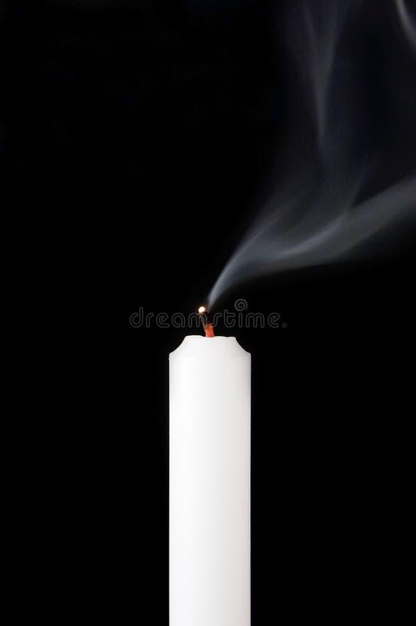 Rook en uitgestorven kaars op een zwarte achtergrond stock foto