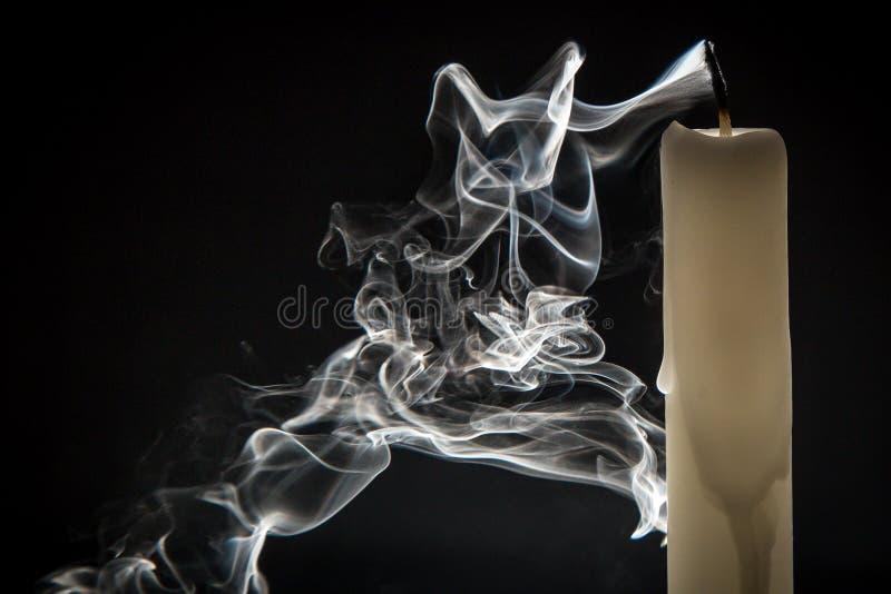 Rook en uitgestorven kaars op een zwarte achtergrond royalty-vrije stock afbeeldingen