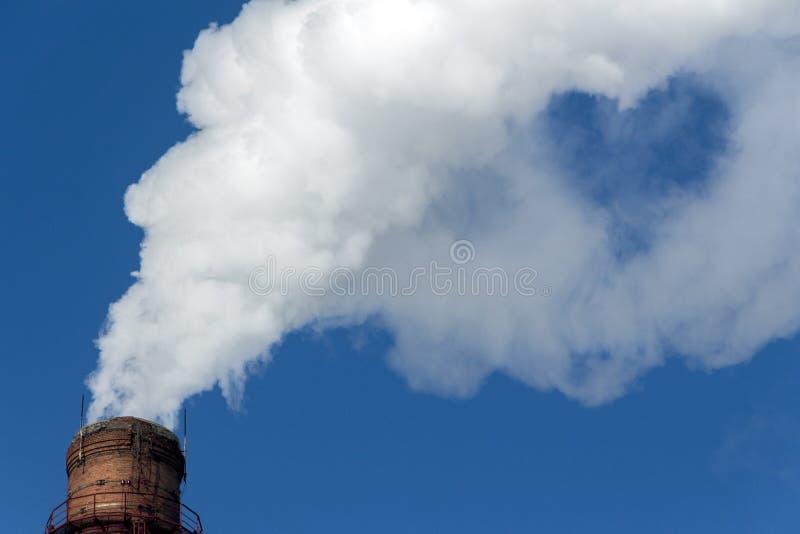 Rook met verspreiding in de vorm van een hart van een industriële pijp in een blauwe hemel De Aard van de conceptenliefde, Ecolog stock foto
