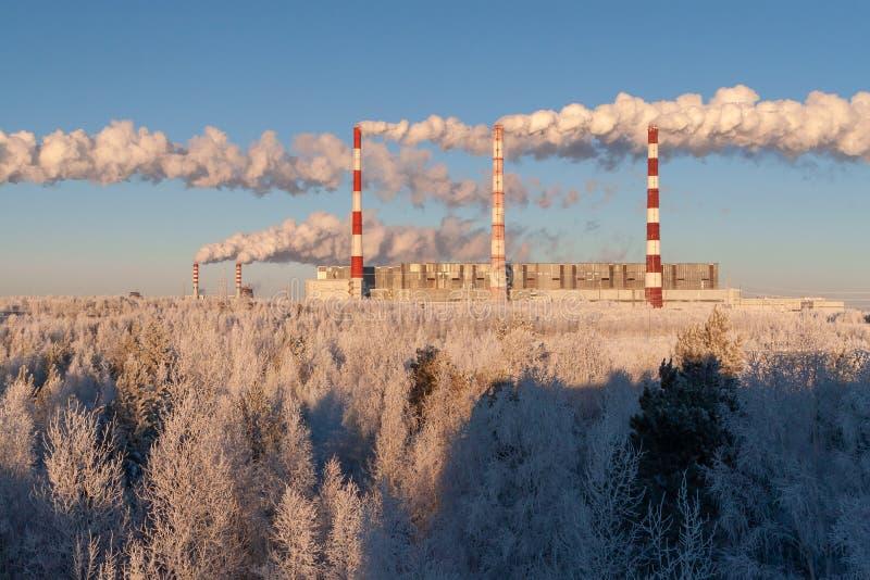Rook van de pijpen van thermische elektrische centrales op de achtergrond van zuivere de winteraard stock foto