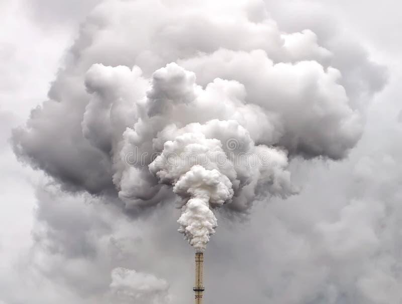Rook van fabriekspijp tegen donkere hemel stock foto's
