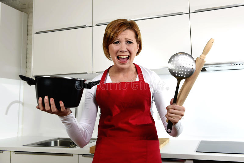 Rookie home cook woman in red apron at home kitchen holding cooking pan and rolling pin screaming desperate in stress royalty free stock images
