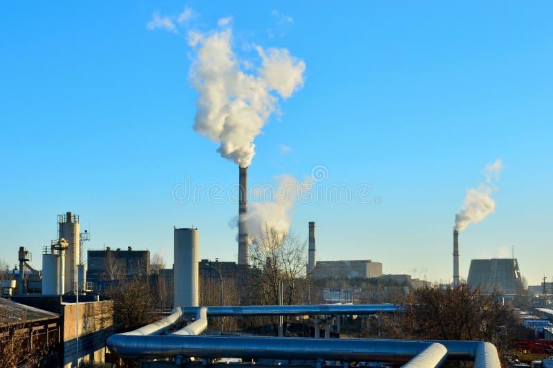 Rooktoren van CHP en blauwe hemel Centrale Elektrische Hitte Buiten pijpleidingen dichtbij Gecombineerde Hitte en Macht stock foto