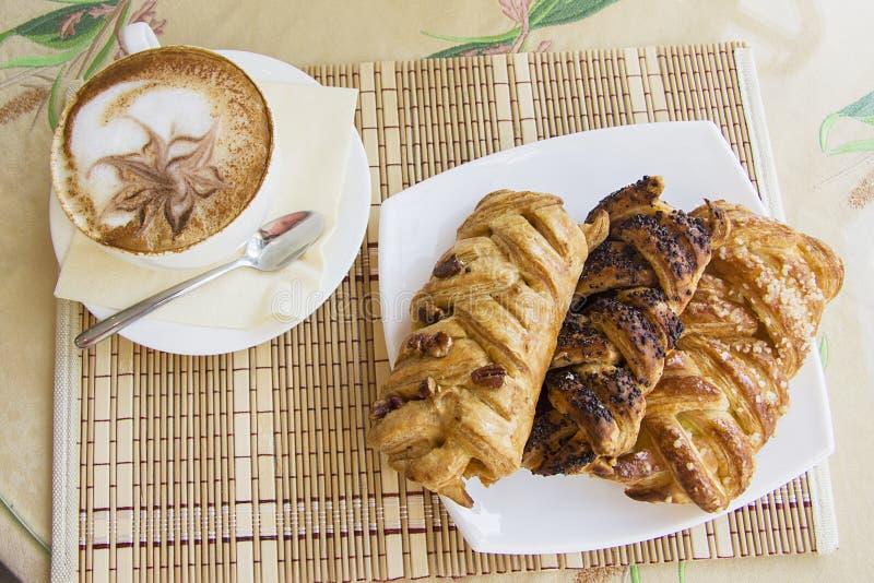 Rookwolkbroodjes en cappucino stock afbeelding