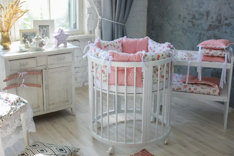 Room for baby, baby round crib. White, pink bedding, peach pillow and quilted blanket, pink rug bright interiors, large Windows, white table and kamod, chairs royalty free stock photography
