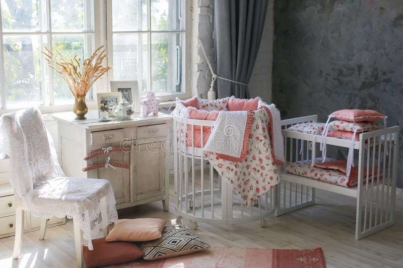 Room for baby, baby round crib. White, pink bedding, peach pillow and quilted blanket, pink rug bright interiors, large Windows, white table and kamod, chairs royalty free stock images