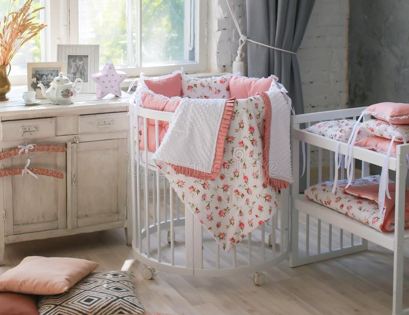 Room for baby, baby round crib. White, pink bedding, peach pillow and quilted blanket, pink rug bright interiors, large Windows, white table and kamod, chairs stock photography