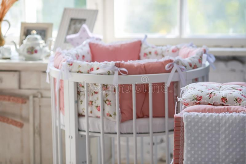 Room for baby, baby round crib. White, pink bedding, peach pillow and quilted blanket, pink rug bright interiors, large Windows, white table and kamod, chairs royalty free stock photos