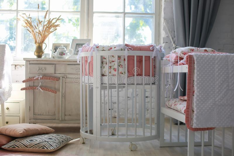 Room for baby, baby round crib. White, pink bedding, peach pillow and quilted blanket, pink rug bright interiors, large Windows, white table and kamod, chairs stock images