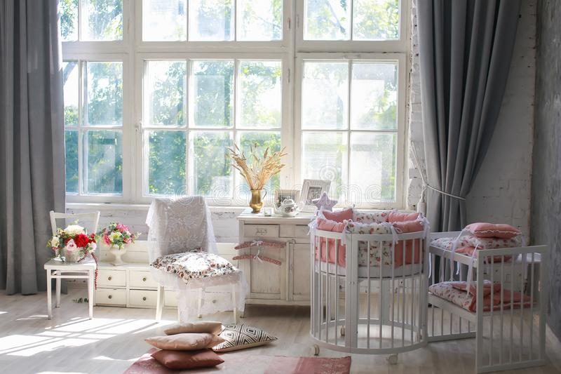 Room for baby, baby round crib. White, pink bedding, peach pillow and quilted blanket, pink rug bright interiors, large Windows, white table and kamod, chairs stock photos