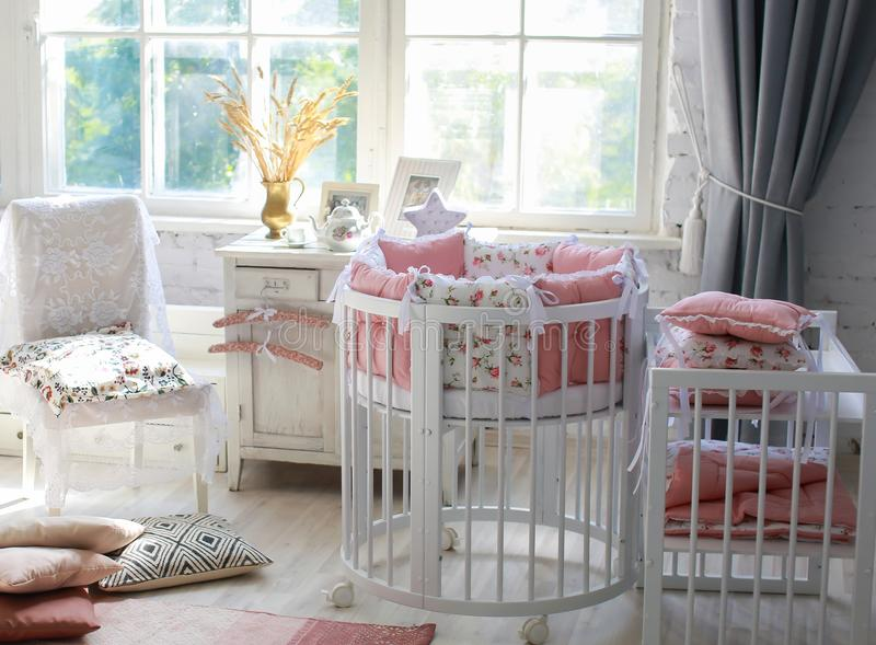 Room for baby, baby round crib. White, pink bedding, peach pillow and quilted blanket, pink rug bright interiors, large Windows, white table and kamod, chairs stock image