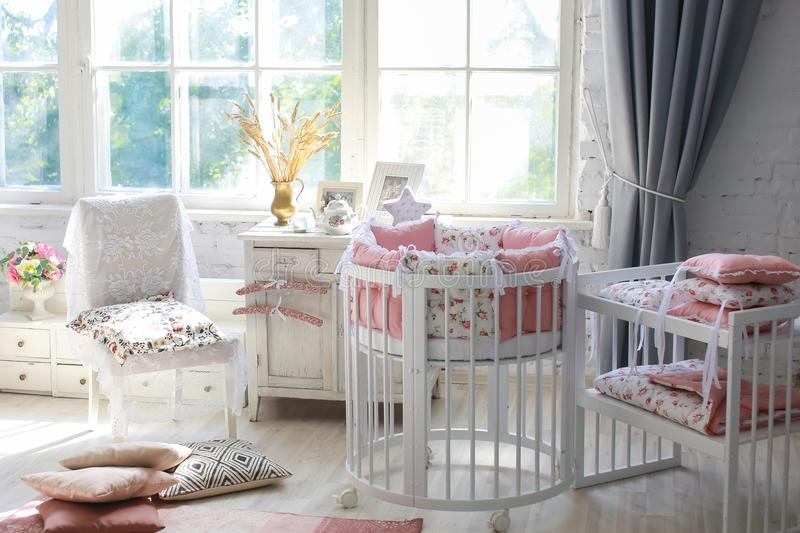 Room for baby, baby round crib. White, pink bedding, peach pillow and quilted blanket, pink rug bright interiors, large Windows, white table and kamod, chairs stock photo