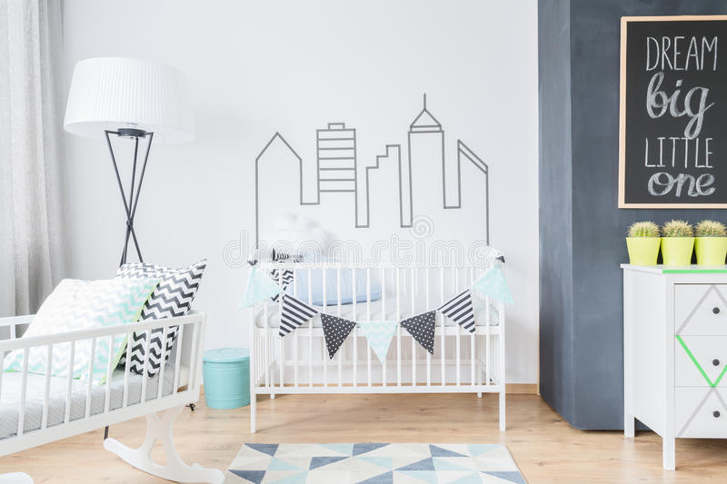 Room for a baby in scandinavian style. Shot of a bright newborn's room with a white crib, wooden floor and black and white walls stock photography