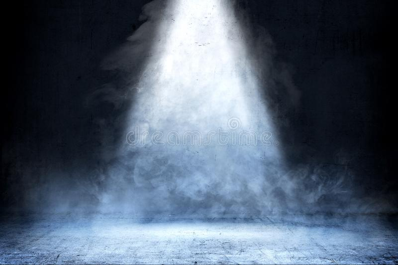 Room with concrete floor and smoke with light from the top. Against dark wall background royalty free stock photo