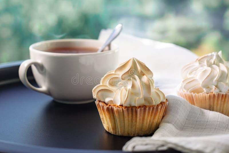 Room cupcakes en een kop thee stock foto