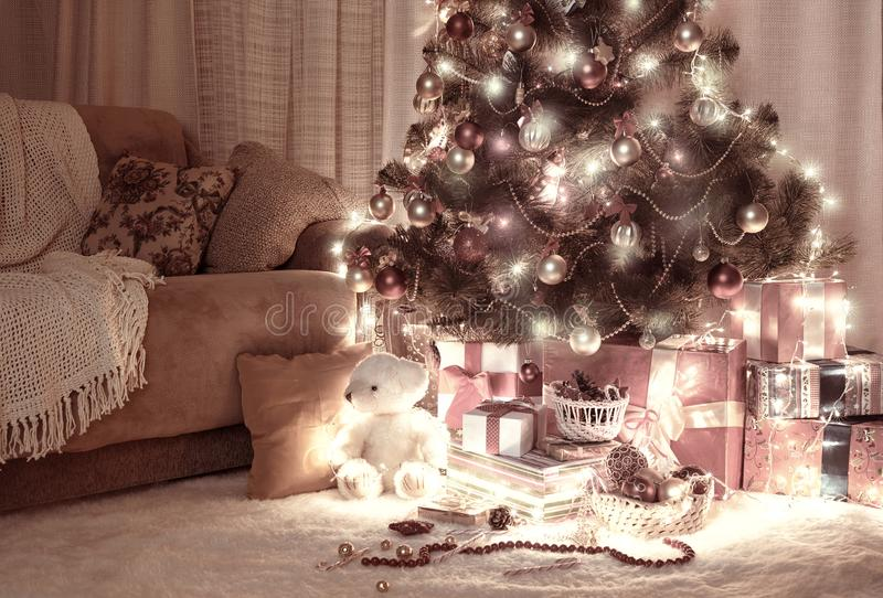 Room in dark with illuminated christmas tree, decoration and gifts, home interior at night, red brown toned stock images