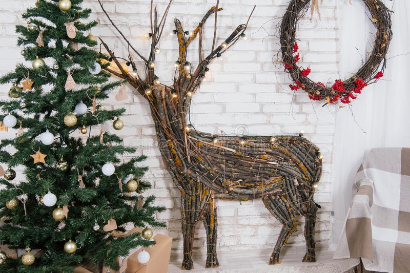 New Year`s location in the studio with a deer, decorated with a Christmas tree, gifts, a basket of cones royalty free stock photography