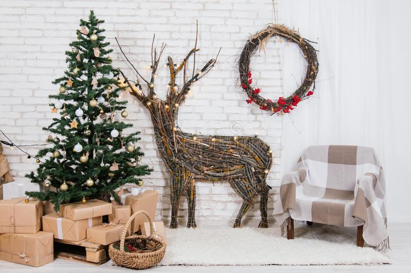 New Year`s location in the studio with a deer, decorated with a Christmas tree, gifts, a basket of cones royalty free stock photos
