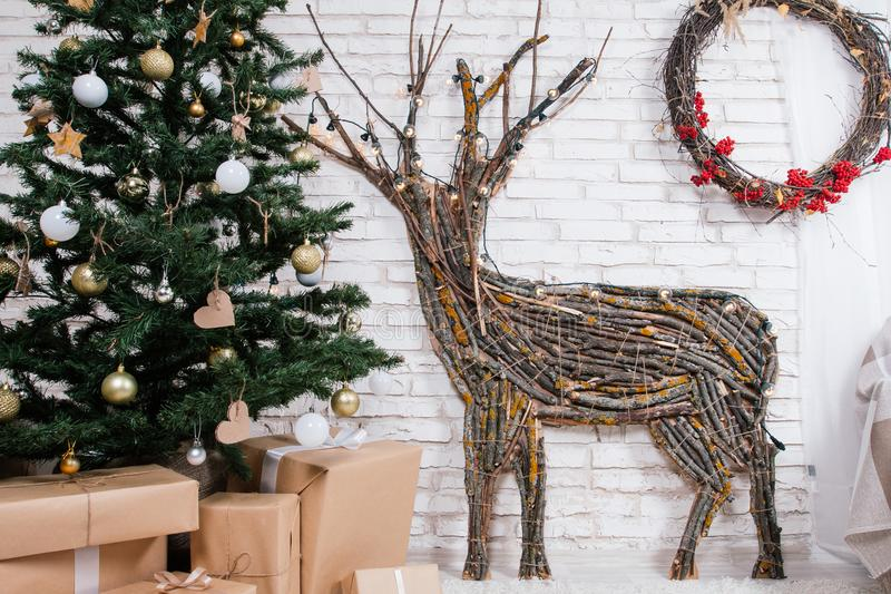 New Year`s location in the studio with a deer, decorated with a Christmas tree, gifts, a basket of cones royalty free stock photo